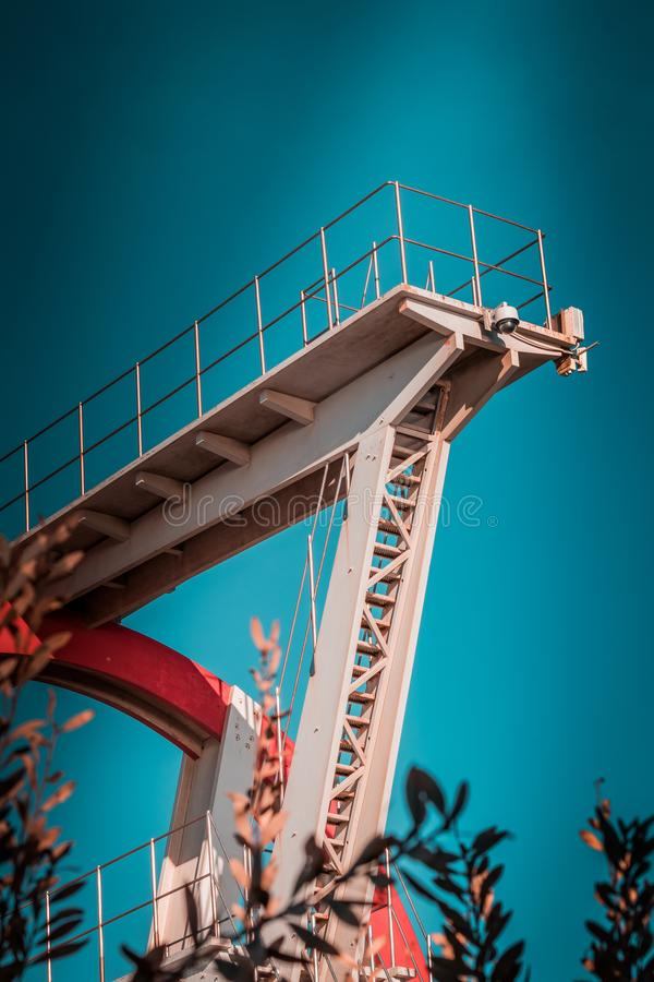 Abandoned metal diving structure. Iconic industrial and sports architecture, white and red steel elements on a deep blue clear sky royalty free stock images