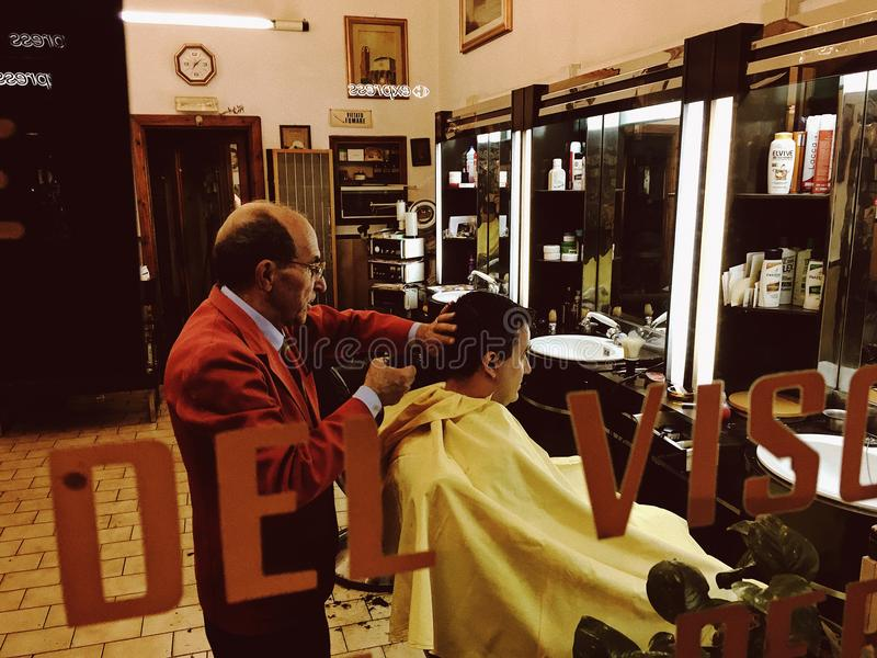 Barber cuts her hair men client. Rome, Italy - October 25, 2017: barber cuts her hair men client royalty free stock photo