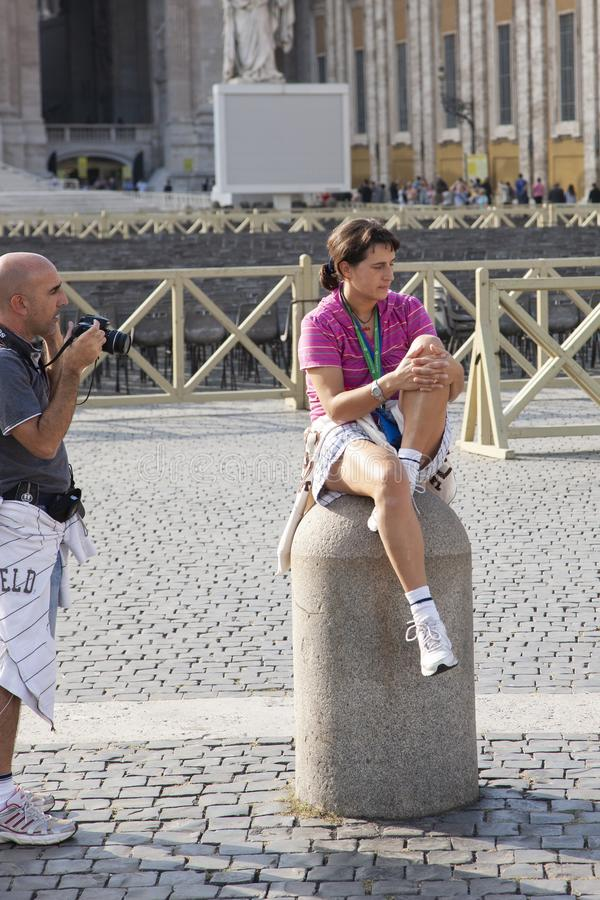 Rome, Italy, October 13, 2011: A young woman sits on a fence in St. Peter`s Square royalty free stock photo