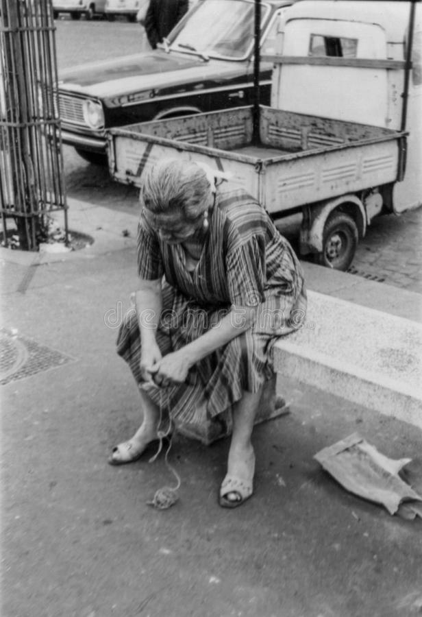 Rome, Italy, 1970 - An old lady thoughtfully unties the knots of a string royalty free stock photos