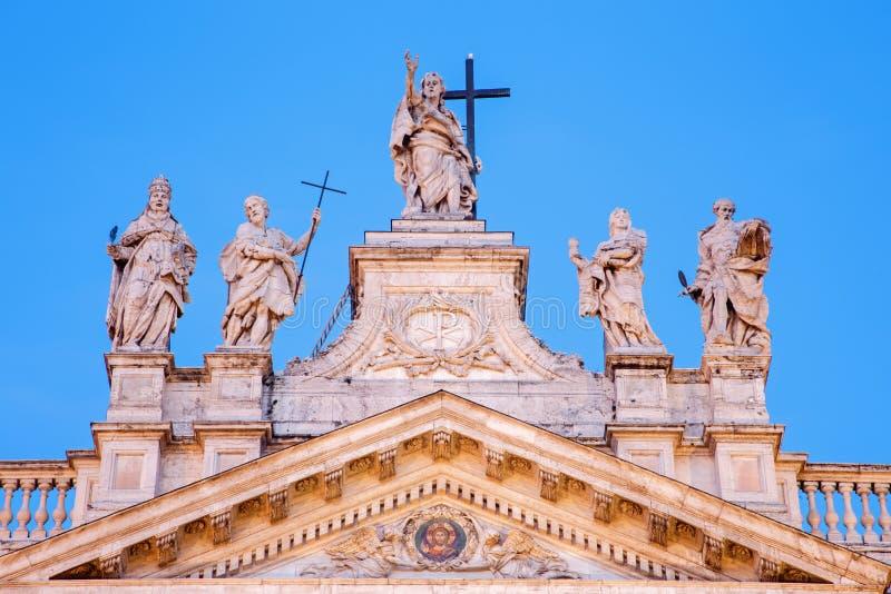Rome - statyn på överkanten av fasaden av basilikan för St John Lateran & x28; Basilikadi San Giovanni i Laterano& x29; på skymni arkivfoton