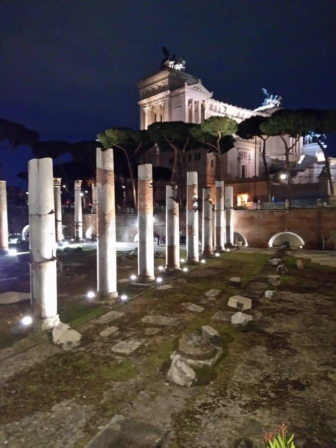 Romerska forntida kolonner med den viktorianska monumentet på bakgrunden arkivbilder
