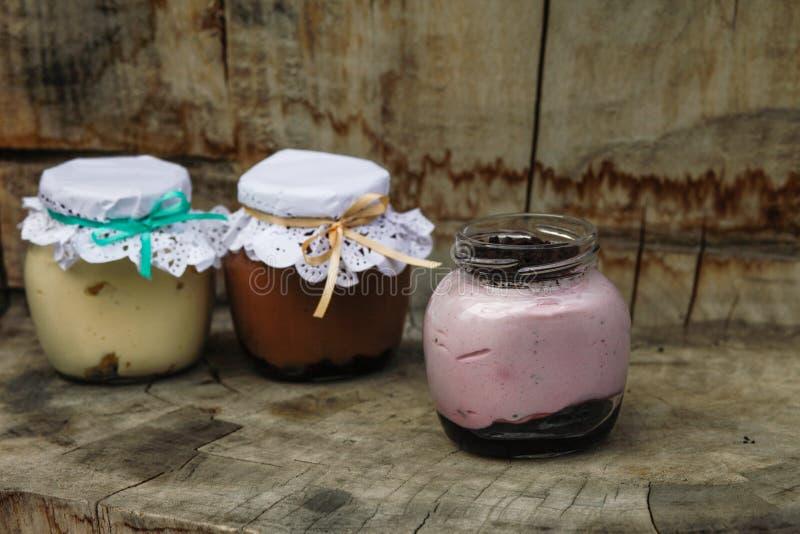 Romig dessert in een kleine glaskruiken met lint op een houten achtergrond stock fotografie