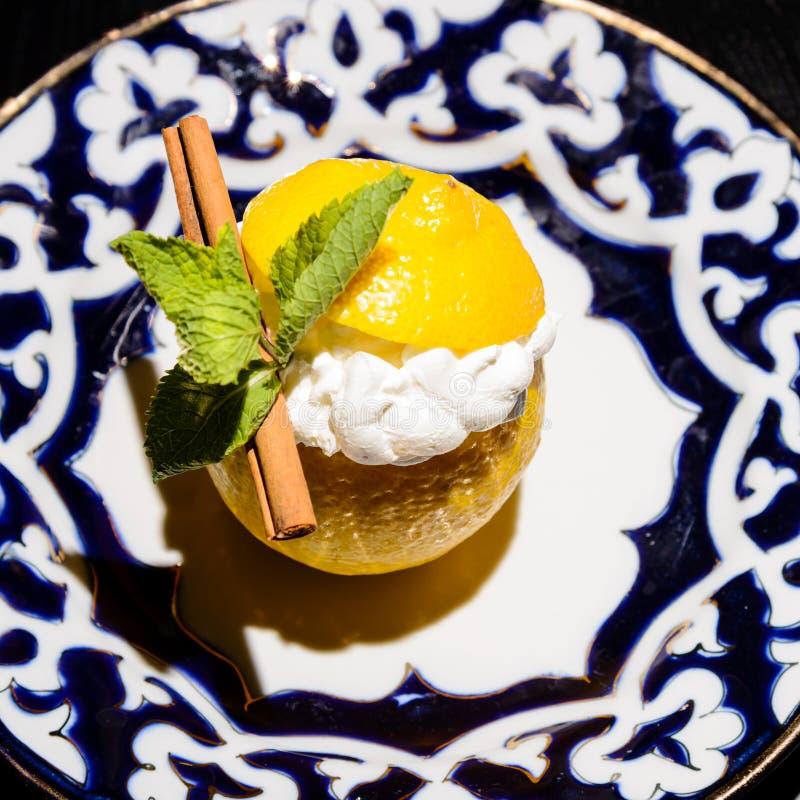 Romig die dessert in de citroenhelften wordt gediend met smintbladeren worden verfraaid stock foto