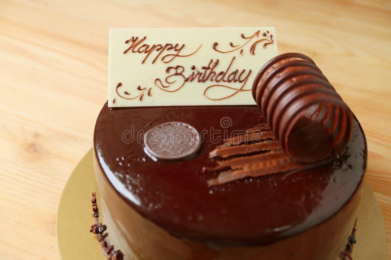 Romig witte die de groetkaart van de chocoladeverjaardag op de cake van de chocolademousse op de houten lijst wordt bedekt royalty-vrije stock afbeelding