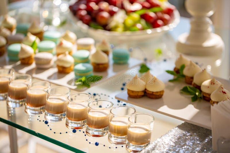 Romige koffielikeur met karamel op een lijst aangaande de achtergrond van cakes stock foto's