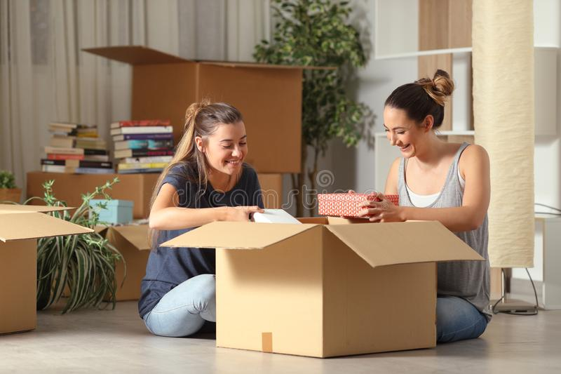 Rommates felizes que unboxing casa movente dos pertences fotografia de stock
