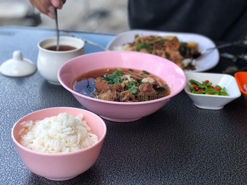 Rompa velocemente con la minestra della radura della carne di maiale in ciotola e riso rosa in tazza rosa, deliziosa di alimento  fotografia stock libera da diritti