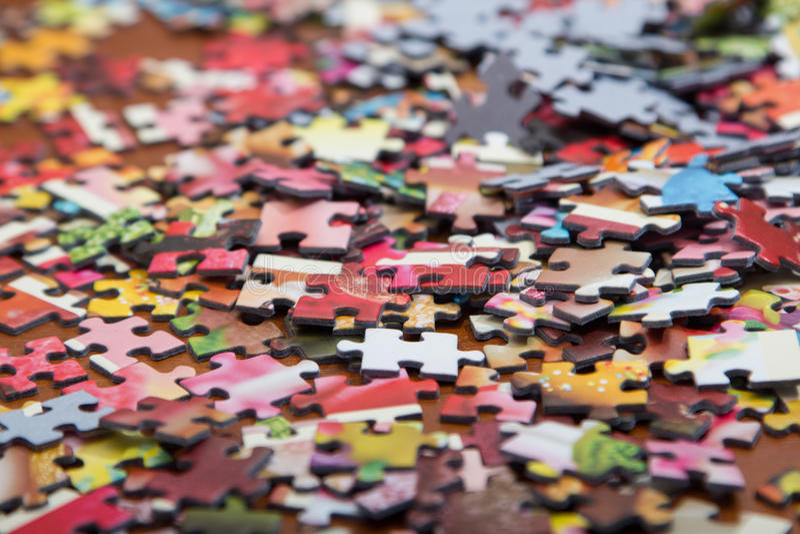 Rompecabezas colorido en el escritorio imagenes de archivo