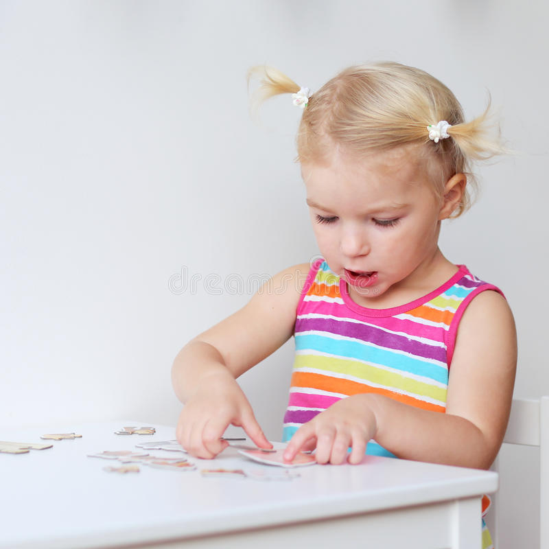Rompecabezas de junta de la niña pequeña dentro imagenes de archivo
