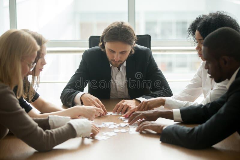 Rompecabezas de junta del equipo diverso de la oficina que ayuda encontrando el negocio s fotos de archivo