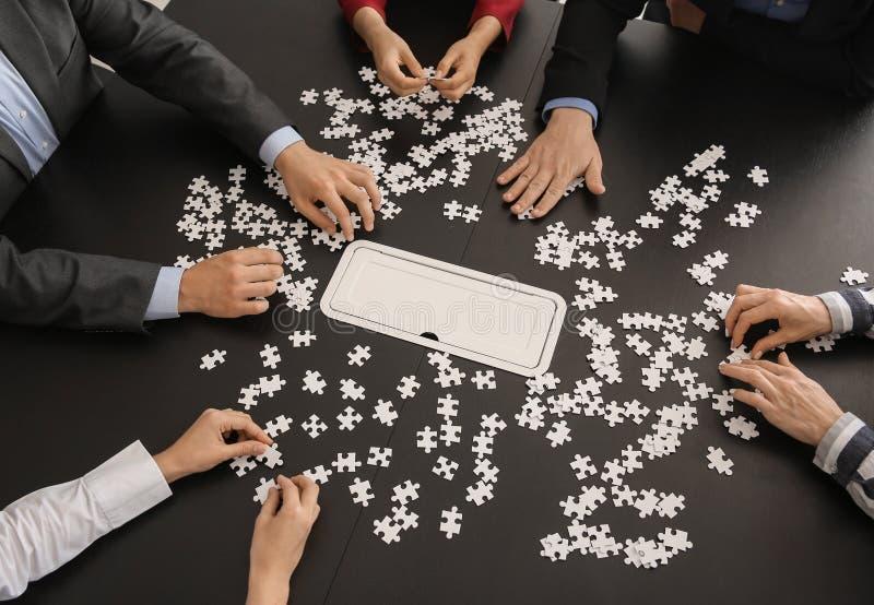Rompecabezas de junta del equipo del negocio en la tabla oscura imagen de archivo