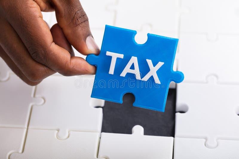 Rompecabezas del impuesto de la tenencia de la mano imagen de archivo libre de regalías