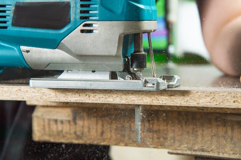 Rompecabezas eléctrico del primer para la madera que asierra un pedazo de madera foto de archivo