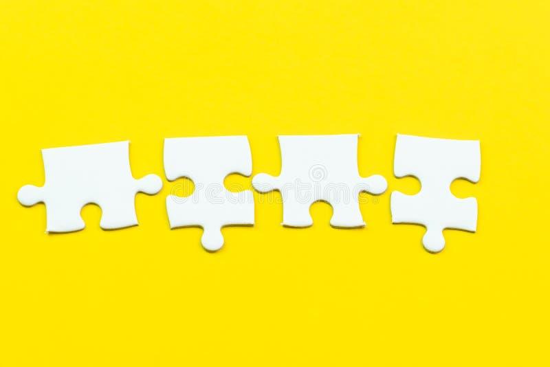 rompecabezas 4 en fondo amarillo sólido usando cosechadora de la cosa importante tan 4 o trabajo junto al éxito o solucionar prob fotos de archivo