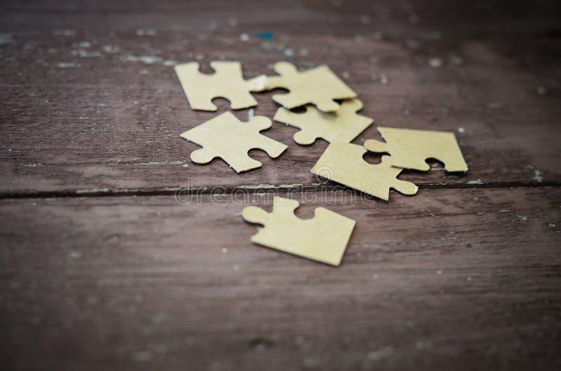 Rompecabezas en fondo de madera imagen de archivo libre de regalías