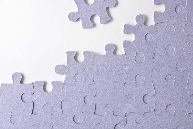 Rompecabezas inacabado púrpura en una tabla blanca imagen de archivo libre de regalías