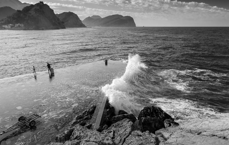 Rompeolas de piedra con las ondas grandes. Montenegro fotos de archivo