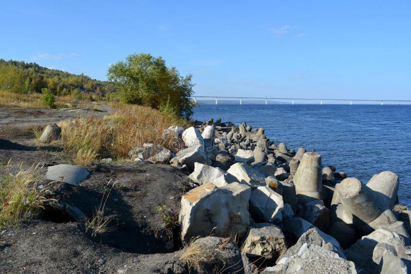 Rompeolas en el banco del r?o Volga Paisaje con las piedras, los árboles y el puente sobre el río imagen de archivo