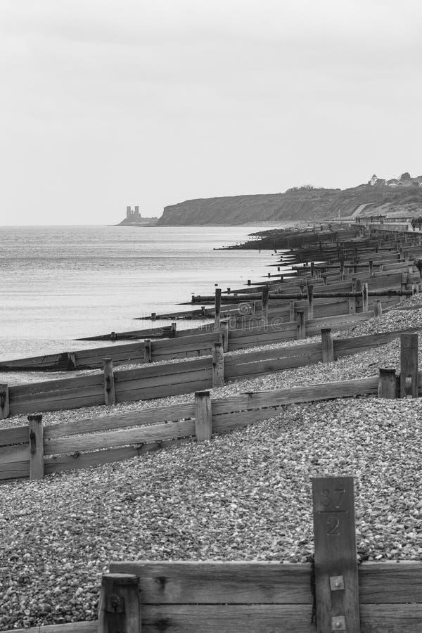 Rompeolas en la playa de la bahía de Herne y torres de Reculver en la distancia imagen de archivo libre de regalías