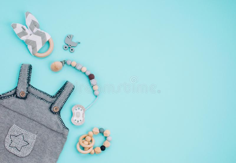 Romper do bebê, soother e brinquedos de madeira no fundo azul fotos de stock royalty free
