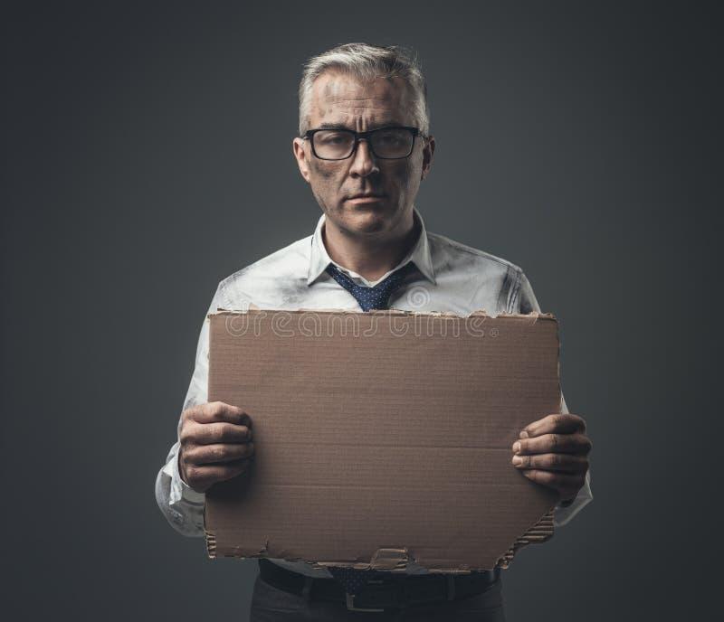 Rompió al hombre de negocios desempleado que llevaba a cabo una muestra de la cartulina foto de archivo libre de regalías