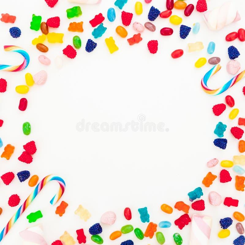 Rond die kader van geassorteerd gekleurd suikergoed op witte achtergrond wordt gemaakt Vlak leg, hoogste mening stock fotografie