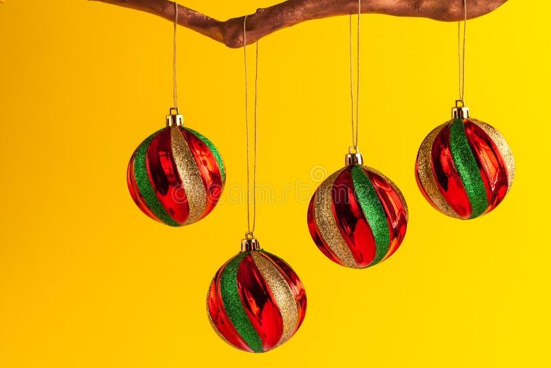 Rond gekleurde Kerstmisornamenten die van gouden tak tegen gele achtergrond hangen royalty-vrije stock fotografie