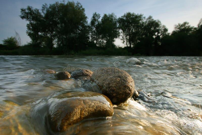 Rond gemaakte stenen in de rivier stock fotografie