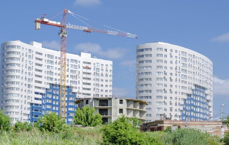 Rond huis in aanbouw op de achtergrond van nieuwe witte gebouwen en blauwe hemel royalty-vrije stock fotografie