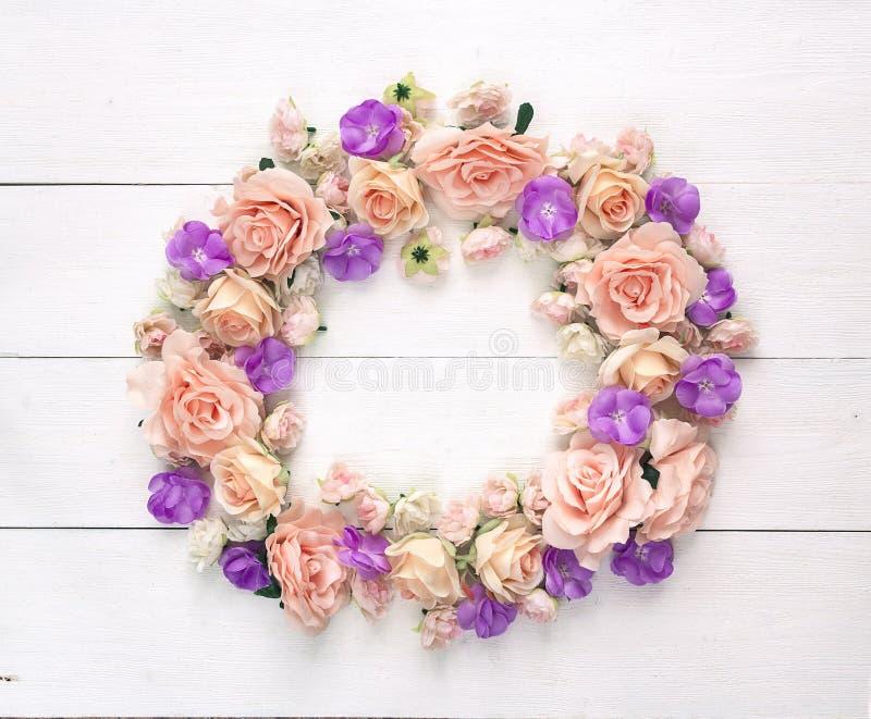 Rond kader van bloemenrozen op een witte houten achtergrond met e stock afbeelding