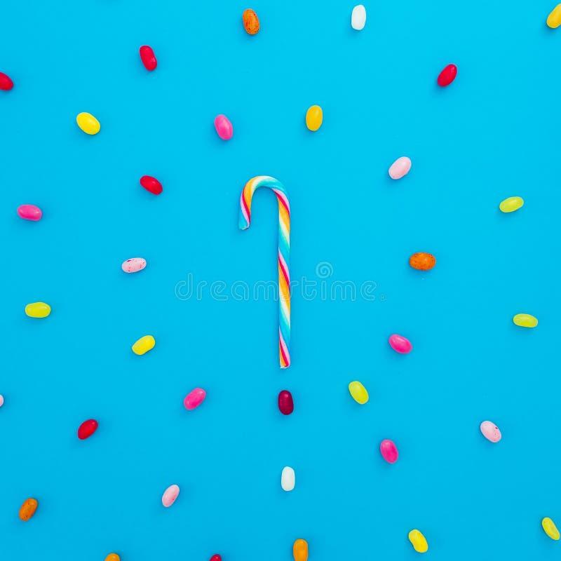 Rond kader van gekleurde suikergoed en regenboogrietsuiker op blauwe achtergrond Vlak leg, hoogste mening stock afbeeldingen