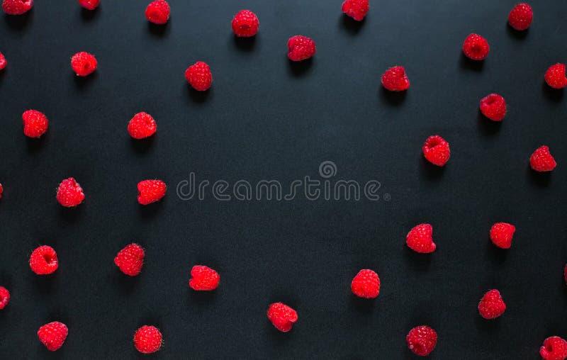 Rond Kader van rode frambozenbessen op zwarte achtergrond stock afbeeldingen