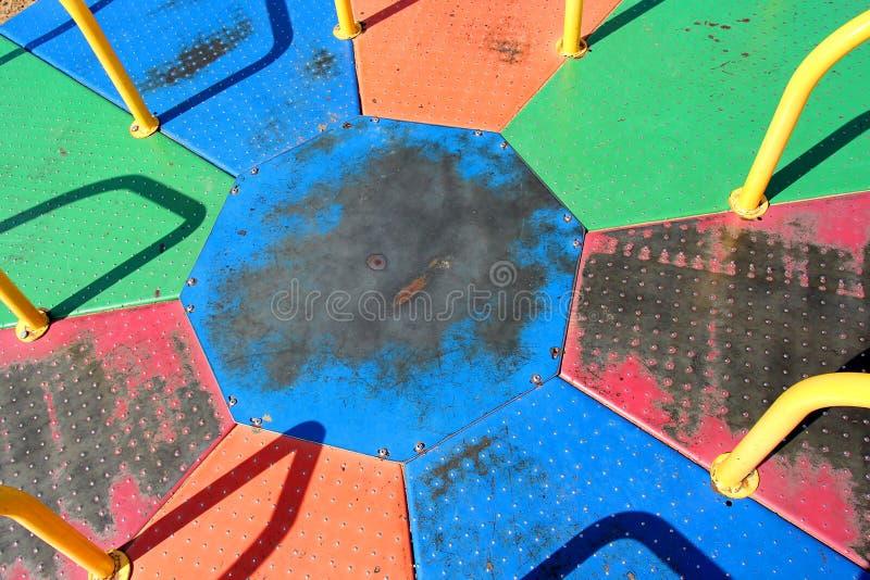 Rond point de manège de terrain de jeu coloré par arc-en-ciel en métal photographie stock