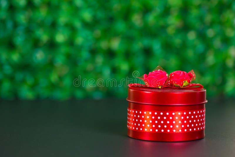 Rond rood giftvakje met lintboog op zwarte lijst en groene achtergrond met exemplaarruimte voor seizoen of groet en vrolijk conce royalty-vrije stock afbeeldingen