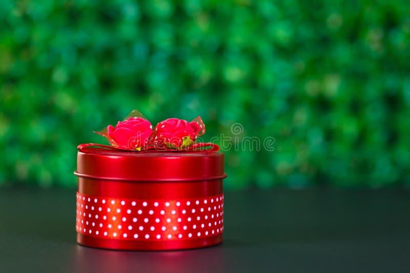 Rond rood giftvakje met lintboog op zwarte lijst en groene achtergrond met exemplaarruimte voor seizoen of groet en vrolijk conce stock afbeelding
