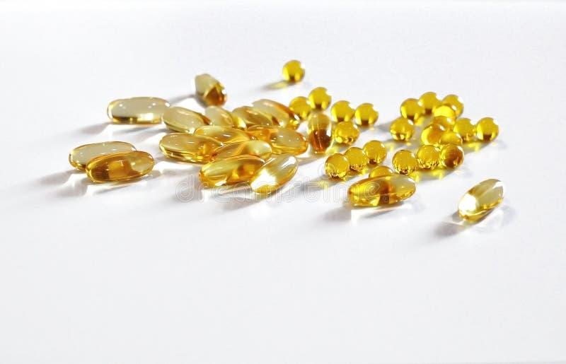 Ronda amarilla transparente y cápsulas oblongas con el aceite de pescado Omega 3, se dispersan que fotos de archivo libres de regalías