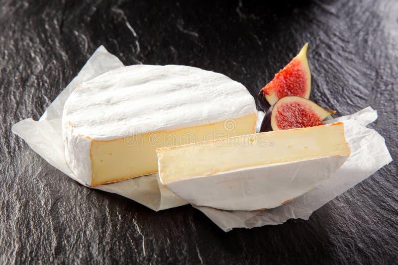 Ronda cortada del queso del camembert con los higos imagenes de archivo