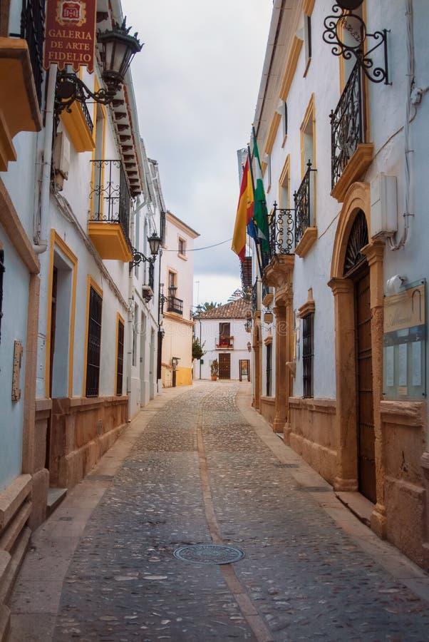 RONDA, ESPAÑA - 3 DE FEBRERO DE 2014: Stre pavimentado piedra estrecha del adoquín imagen de archivo libre de regalías