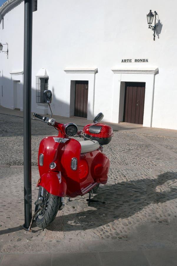 Ronda, Spagna, febbraio 2019 Un vecchio motorino rosso italiano ? parcheggiato vicino all'attrazione principale di Ronda - l'aren immagini stock libere da diritti