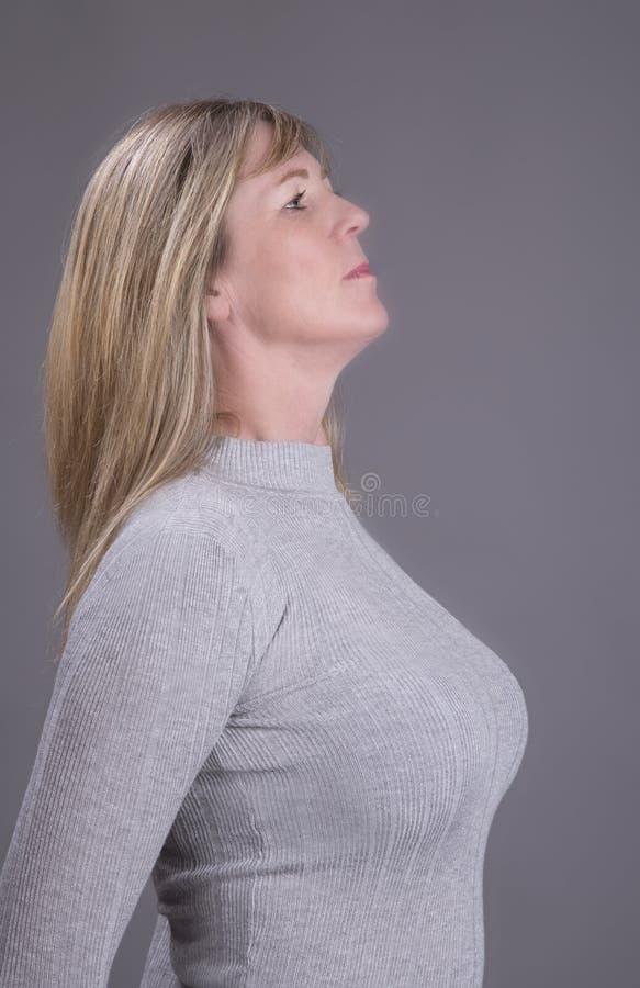 Rondborstige blonde vrouw in grijze sweater royalty-vrije stock foto's