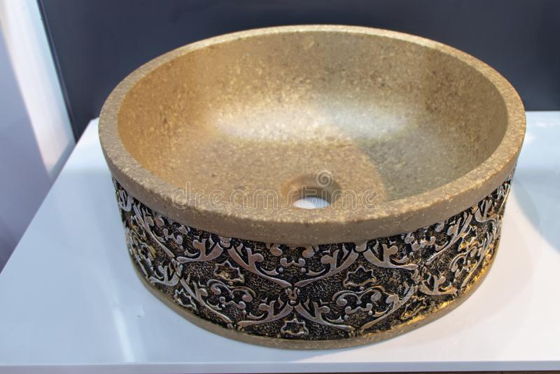 Ronde antieke die gootsteen van steen wordt gemaakt Gesneden patroon op de gootsteen in brons stock foto
