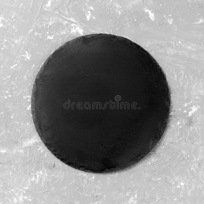 Ronde auf Tabelle schwarzer Teller auf grauem Zementhintergrund Kopieren Sie Platz stockbilder