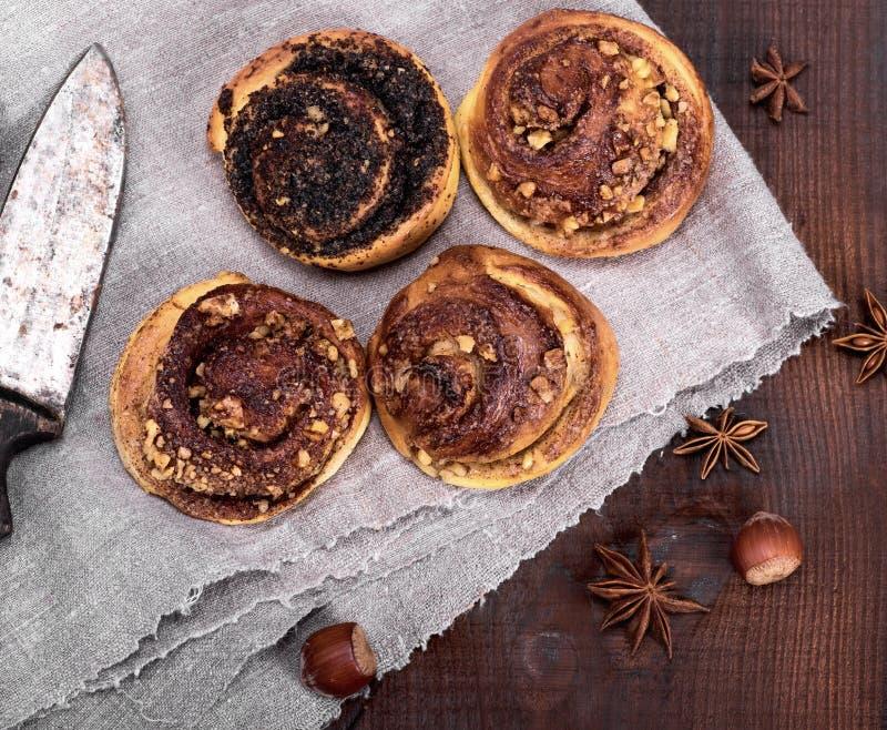 Ronde broodjes met kaneel en papavers op een grijs textielservet royalty-vrije stock foto