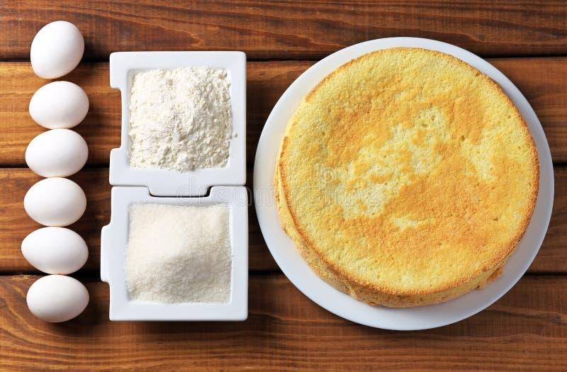 Ronde eigengemaakte koekjescake op een plaat, een bloem, een suiker en eieren stock fotografie