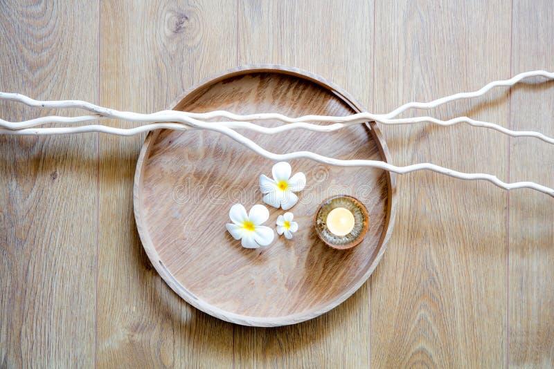 Ronde houten dienblad en takjes, witte mooie bloemen en kaars stock afbeelding