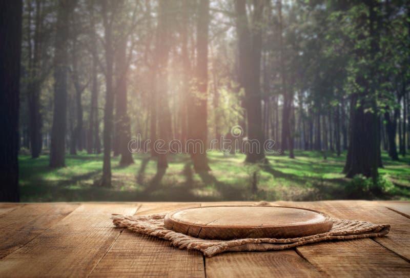 Ronde houten raad op houten lijst aangaande bosachtergrond stock foto