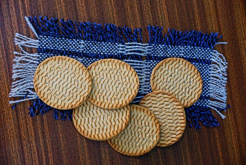 Ronde koekjes op een wolservet op een bruine lijst stock afbeelding