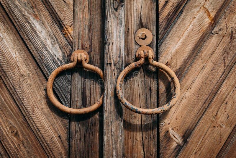 Ronde metaalhandvatten op gesloten oude antieke houten poort of deur stock afbeeldingen