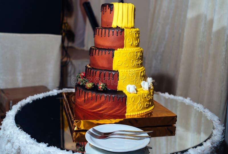 Ronde multi tiered gele en bruine huwelijkscake met aardbeien, rozen en chocoladesuikerglazuur Plaat en vork dichtbij de cake stock afbeeldingen